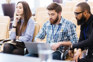 Multiethnic group of young business people using laptop sitting on meeting in conference hall - Looking for Sponsors? How to Find Backers for Your Event